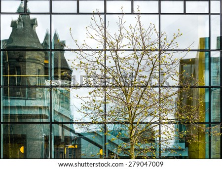 modern office building exterior with many windows, reflexions and trees - stock photo