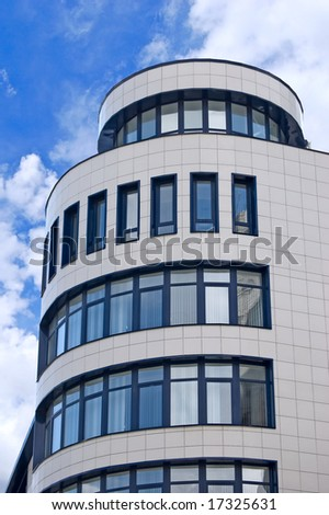 Modern office building on blue sky background - stock photo