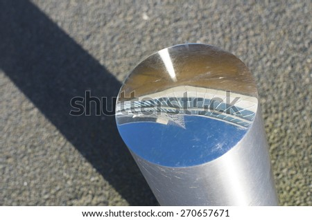 modern office building reflected in a metallic street pole - stock photo