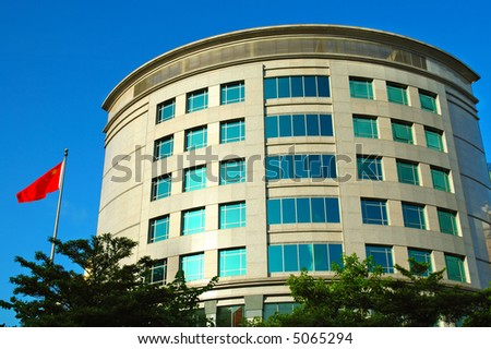 Modern office building with a flag over blue sky - stock photo