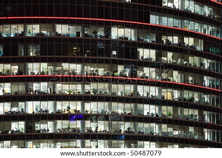 modern office building with big windows at night, in windows light shines - stock photo