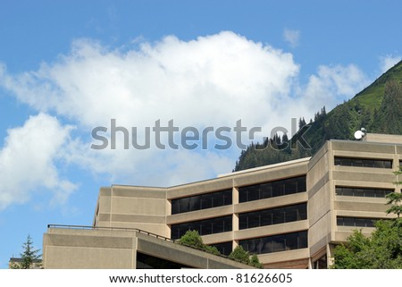 Modern office building with clouds and blue sky in the background
