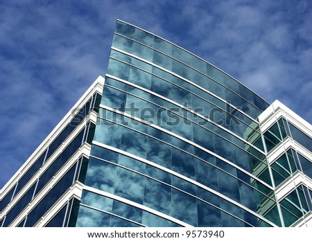 Modern office building with clouds reflected in windows - stock photo