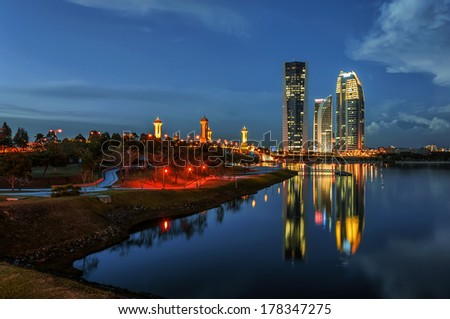 Modern office buildings by Putrajaya Lake, Malaysia at sunset