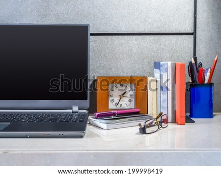 Modern office desk with laptop and office supplies - stock photo