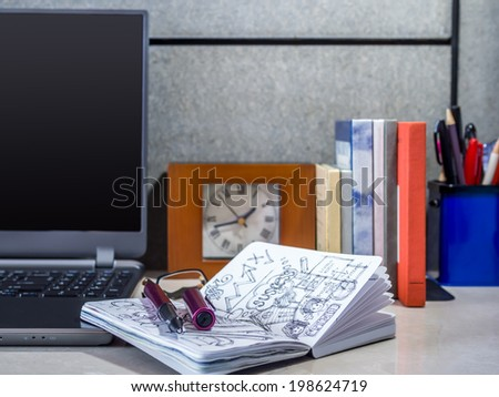 Modern office desk with laptop and sketch book - stock photo