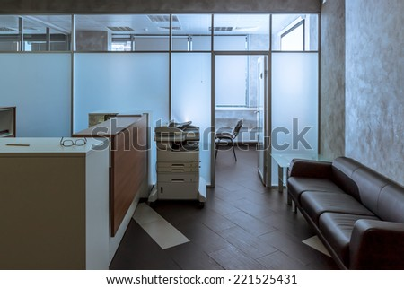 modern office entry hall with reception desk, a couch and copy-machine - stock photo
