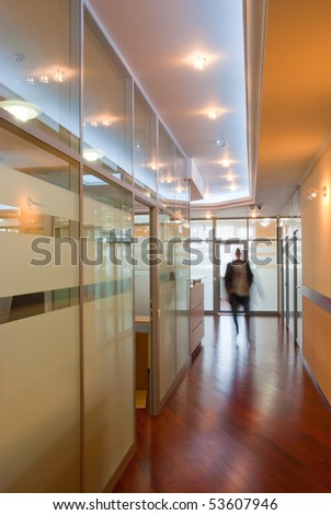 Modern office interior - perspective of a  corridor with a ghost figure of a businessman - stock photo