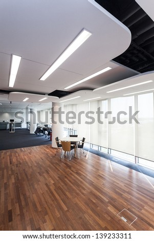 Modern office with design lighting and wooden floor.