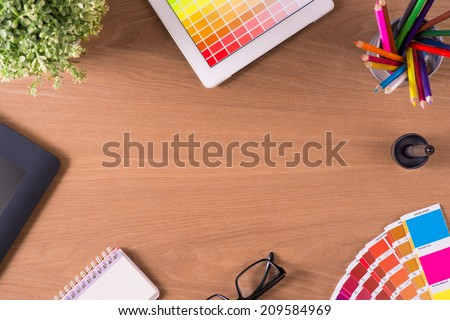 Modern office workplace with digital tablet, notepad, colorful pencils, glasses, graphic tablet, stylus, cup of coffee, and color swatches on a desktop. View from the top