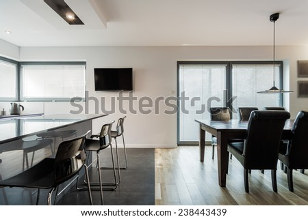 Modern open kitchen and dining room with long table - stock photo