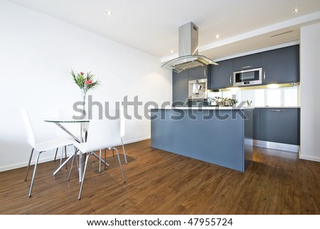Modern open plan living area with dining table and fully fitted kitchen - stock photo