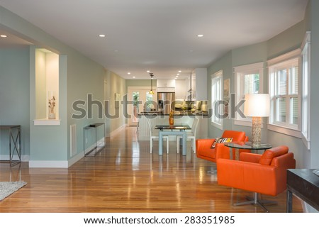 Modern orange chairs in Luxury Modern Living Room with dining table and open kitchen. - stock photo