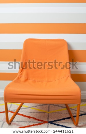 Modern orange fabric armchair - stock photo