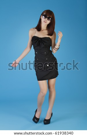 Modern oriental beauty posing, full length portrait on blue background. - stock photo