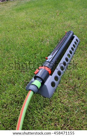 Modern oscillating sprinkler on the mown lawn in the summer garden