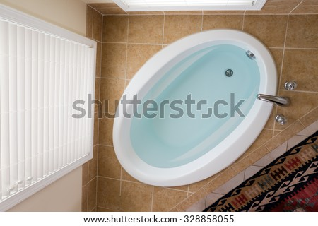 Modern oval domestic bathtub full of clean water in a brown tile surround below a tall window with blinds viewed from above - stock photo