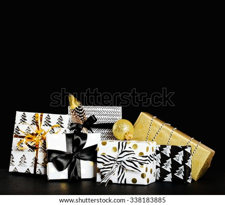 Modern painted paper black and white presents wrap with  bow on a black background - stock photo