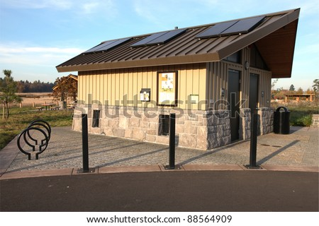 Modern park restroom facility with solar panels. - stock photo
