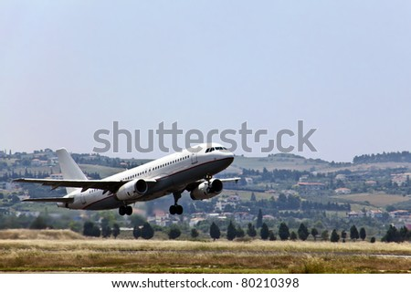 Modern passenger jet airplane landing at urban airport. - stock photo