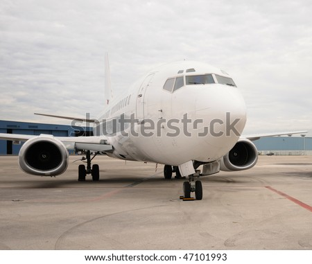 Modern passenger jet airplane on the ground nose view