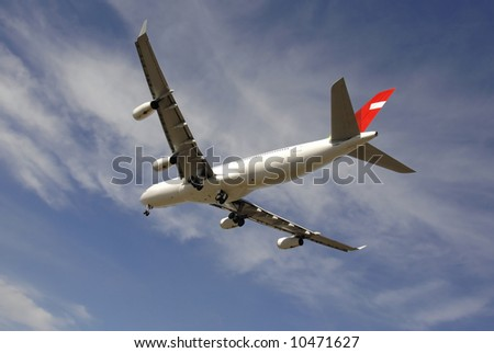Modern passenger jetliner landing against blue sky