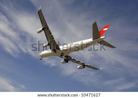 Modern passenger jetliner landing against blue sky - stock photo