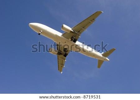 Modern passenger jetliner taking off against blue sky - stock photo