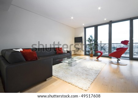 Modern penthouse living room with large leather sofa and floor to ceiling windows - stock photo