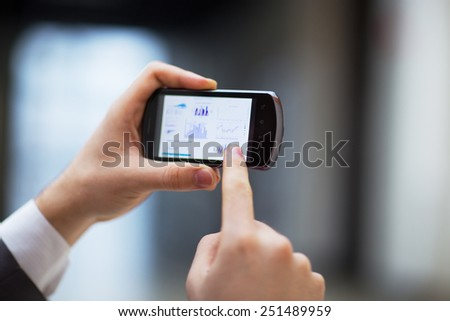 Modern people doing business, graphs and charts being demonstrated on the screen of a phone - stock photo