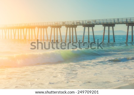 Modern pier during sunny bright day and wavy ocean, vibrant colors - stock photo