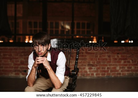 Modern portrait of brutal bearded man sitting on a chair in loft interior. Expressive emotions. Copy space, selective focus. - stock photo