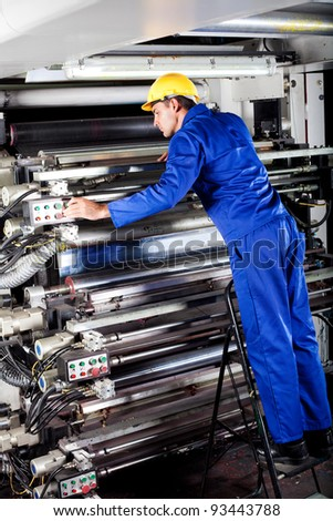 modern printing machine operator checking machine - stock photo