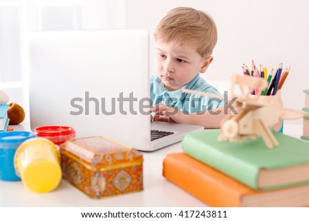 Modern problem: kids and computers. Little boy using laptop. Nice white interior with table full of educational interesting toys - stock photo