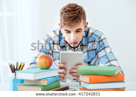 Modern problem: youth and computers. Young student using tablet computer while studying. Nice white interior with table full of books - stock photo