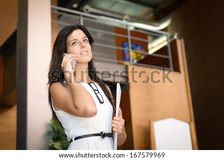 Modern professional businesswoman calling by cellphone in corporate building. - stock photo