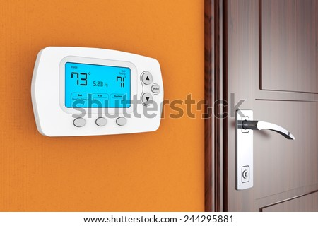 Modern Programming Thermostat on a wall near door - stock photo
