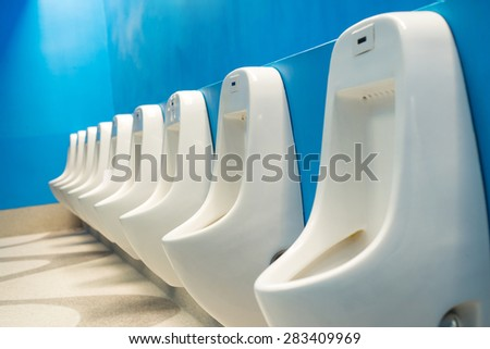 Modern public toilets Interiors A row of urinals urinating on a blue background - stock photo