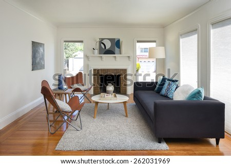 Modern quaint living room interior with fire place, designer chairs, white round table, rug and couch with blue pillows.  - stock photo