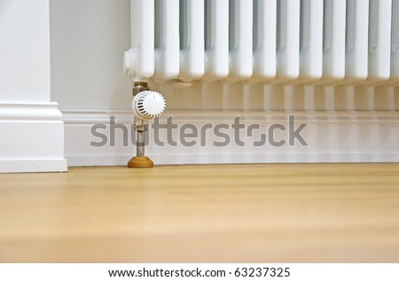 modern radiator at the wall and parquet floor - stock photo