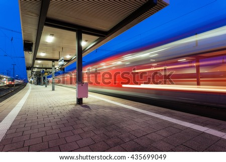 Modern railway station with high speed passenger train on railroad track in motion at night  in Nuremberg, Germany. Fast red commuter train.. Industrial landscape - stock photo