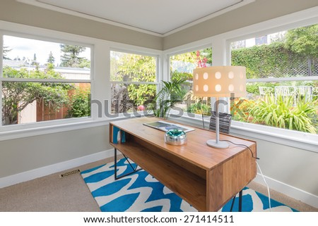 Modern rectangle wooden desk and table desk lamp in glass house style home office surrounded by green garden. Work-space table standing on blue zig zag pattern rug. - stock photo
