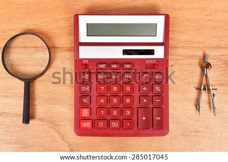 Modern Red Calculator, magnifying glass and compass - stock photo