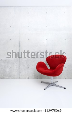 modern red chair and concrete wall - stock photo