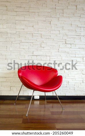 Modern red chair in front of the wall - stock photo