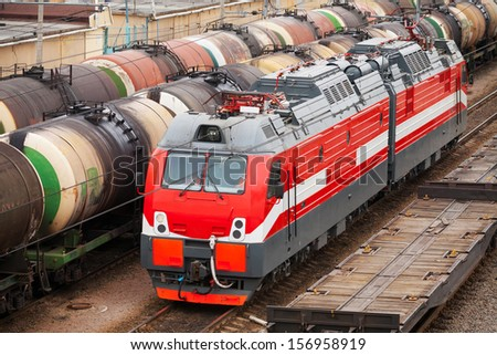 Modern red diesel electric locomotive rides on railway tracks with freight coaches - stock photo