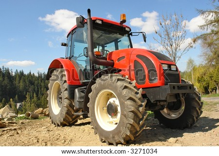 Modern red farm tractor parked