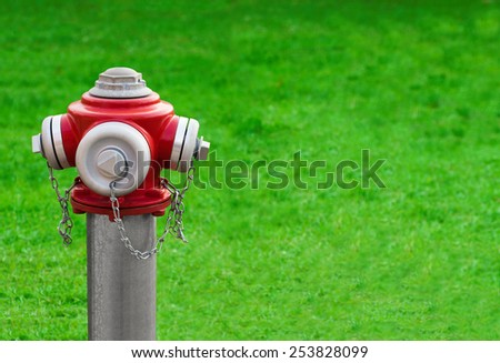 Modern red hydrant on a green grass background with space for text - stock photo