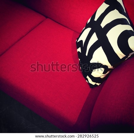 Modern red sofa with decorative black and white cushion. - stock photo
