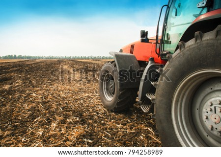 Modern red tractor in the field close-up on a bright sunny day